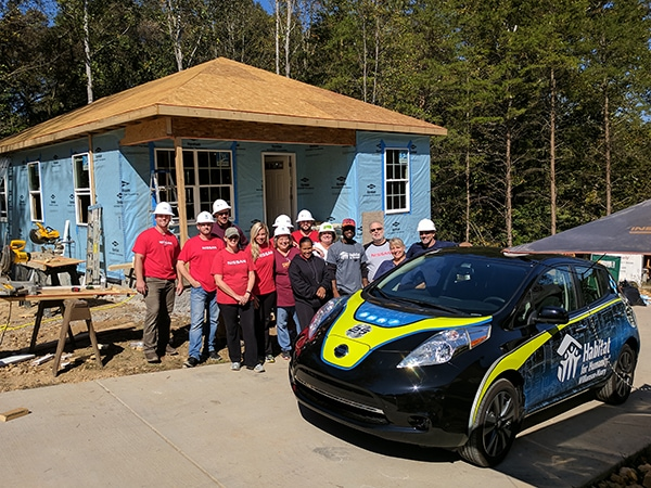 Nissan volunteer team next to the new Nissan Leaf with custom wrap. - 12-Point SignWorks - Franklin, TN
