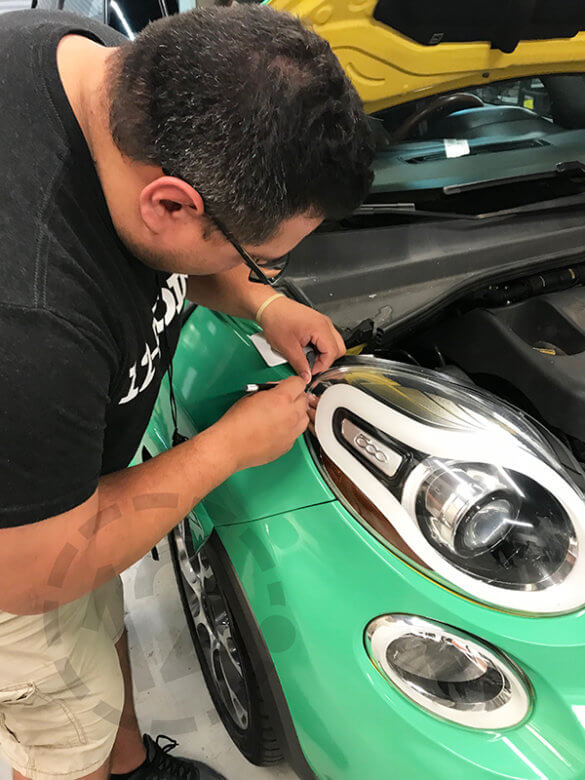 Applying vinyl wrap around headlights. 12-Point SignWorks - Franklin, TN