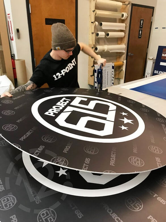 Inserting grommets in Project 615 custom signs by 12-Point SignWorks in Franklin, TN.