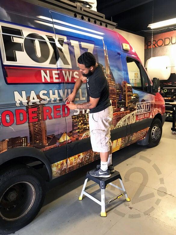 Installing perforated window vinyl on WZTV Fox 17's satellite van wrap at 12-Point SignWorks in Franklin, TN.