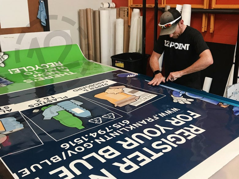 Cutting vinyl for vehicle wraps to promote the City of Franklin's Blue Bin Recycling program installed by 12-Point SignWorks.