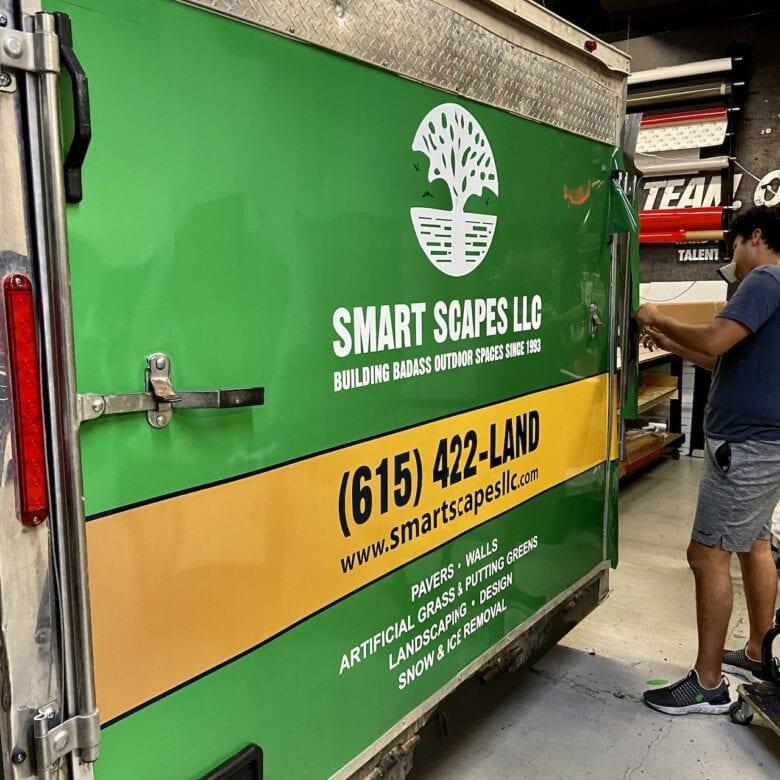 12-Point Team Member Installing Trailer Wraps for Smart Scapes LLC